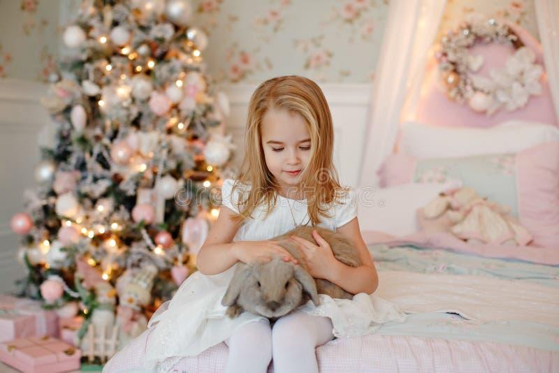 Blonde avec du charme très gentille de petite fille dans les rires blancs de robe et photographie stock libre de droits
