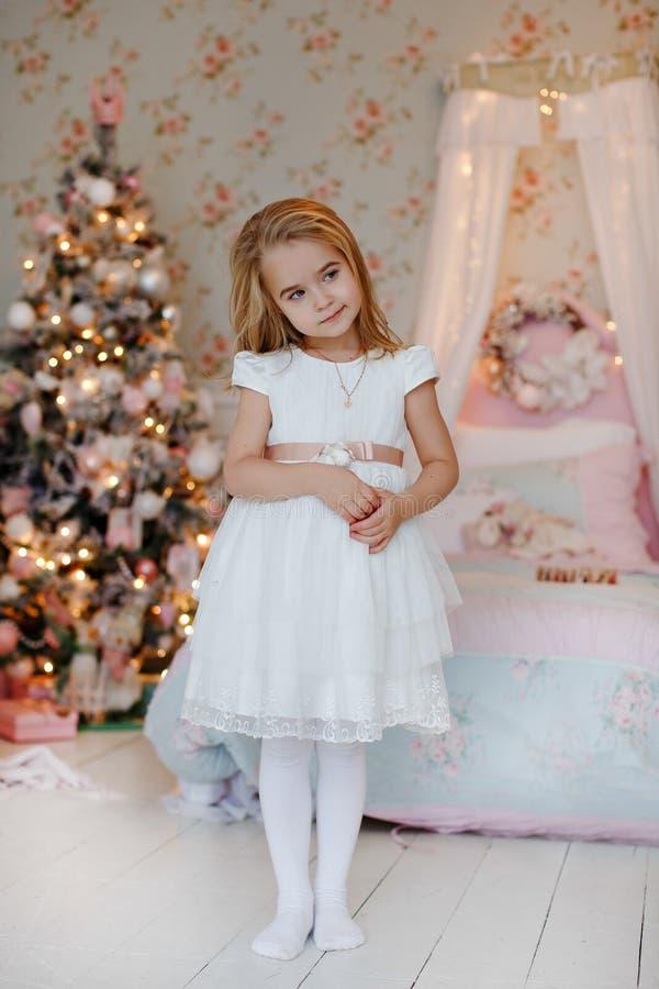 Blonde avec du charme très gentille de petite fille dans une position blanche de robe photos libres de droits