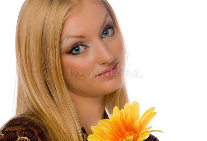 Blonde avec la fleur de yelllow d'isolement photographie stock libre de droits
