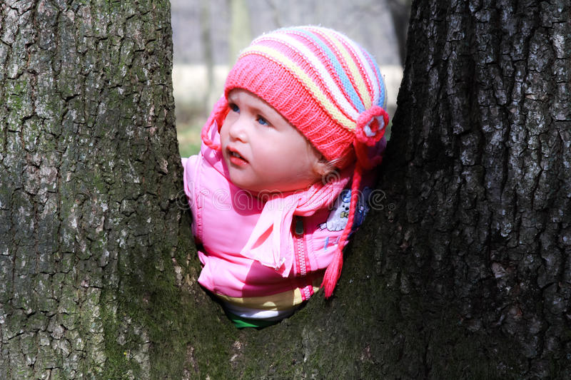 Blonde baby girl. Blonde blue eyed baby girl is playing in the forest royalty free stock photo