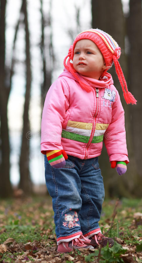 Blonde baby girl. Blonde blue eyed baby girl is playing in the forest royalty free stock image