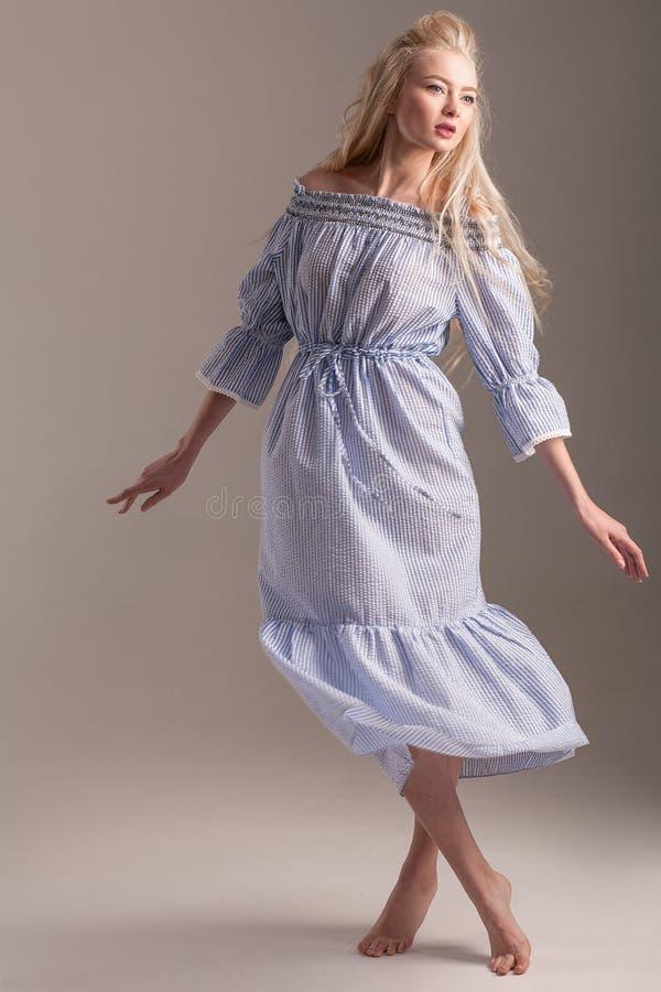 Barefoot model in blue dress posing on gray background. stock image