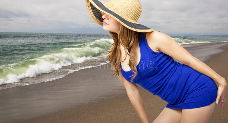 Blonde on the beach. Classy young blond woman with straw hat and old fashioned classic bathing suit looks over the secluded sandy Pacific coast beach near San royalty free stock image