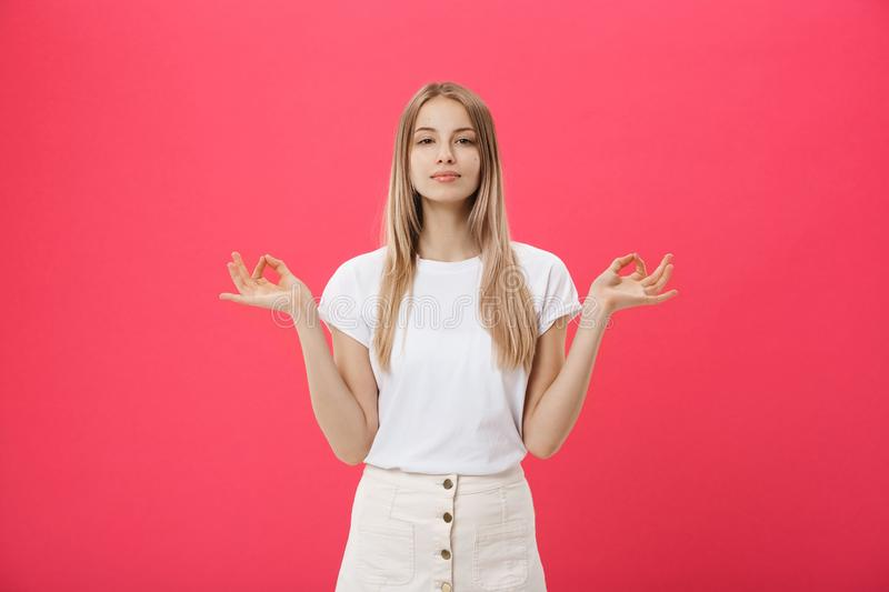 Blonde beauiful young female makes mudra sign, relaxes after hard working day, keeps eyes shut, practises yoga against. Pink background. Young pretty woman royalty free stock photo