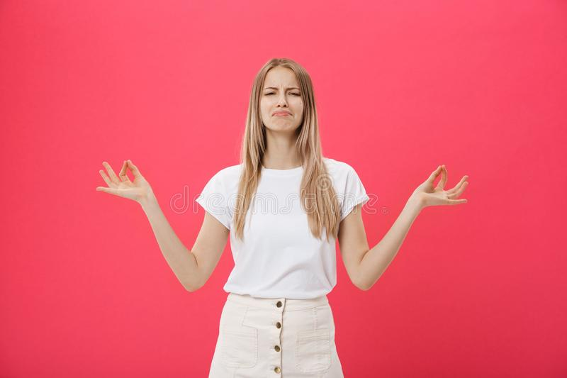 Blonde beauiful young female makes mudra sign, relaxes after hard working day, keeps eyes shut, practises yoga against. Pink background. Young pretty woman royalty free stock images