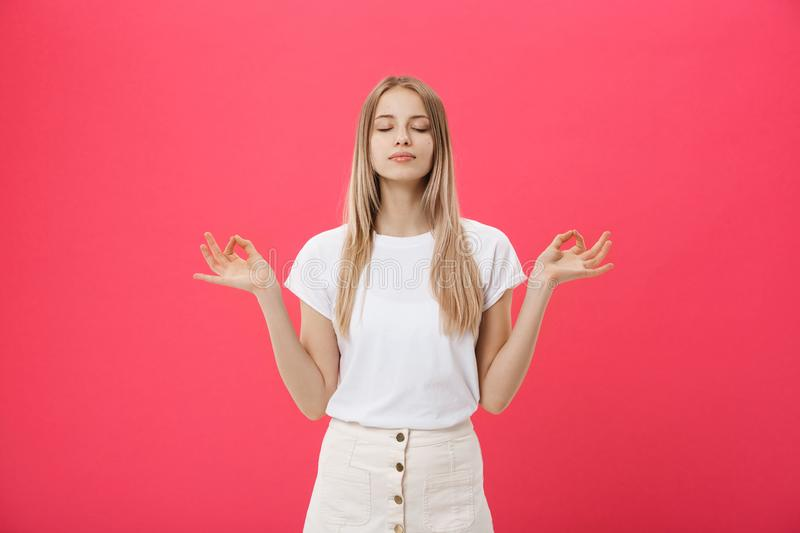 Blonde beauiful young female makes mudra sign, relaxes after hard working day, keeps eyes shut, practises yoga against. Pink background. Young pretty woman royalty free stock photography