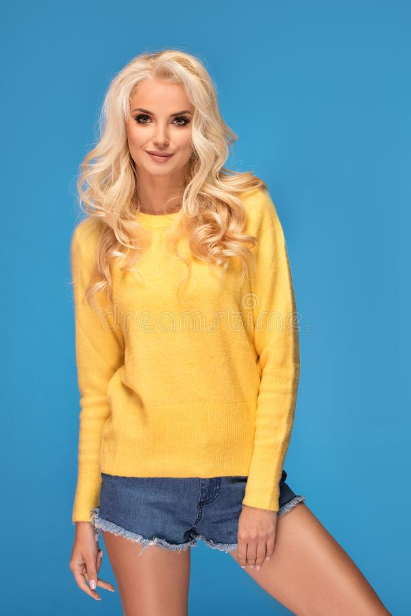 Blonde girl in yellow sweater stock images