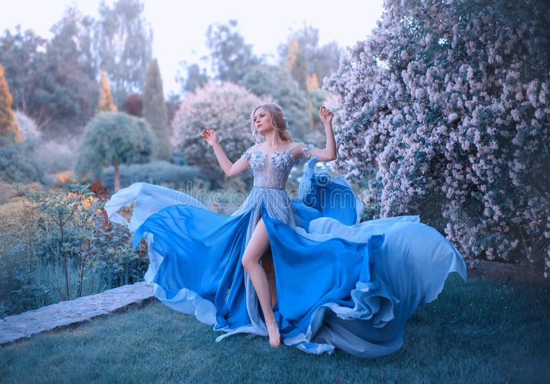 Blonde, with a beautiful elegant hairdo, walks in a fabulous blooming garden. Princess in a long gray-blue dress with a. Long train that flutters in the wind royalty free stock image