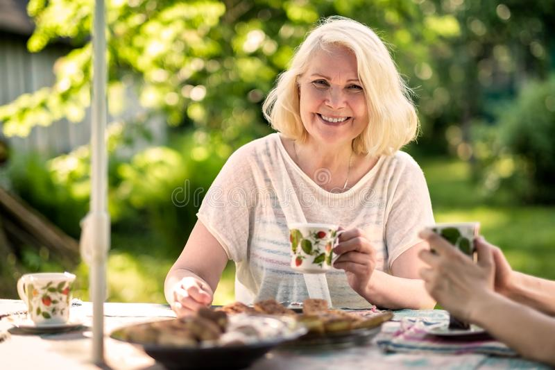 Blonde beautiful grandmother relaxing with her family at the garden stock photo