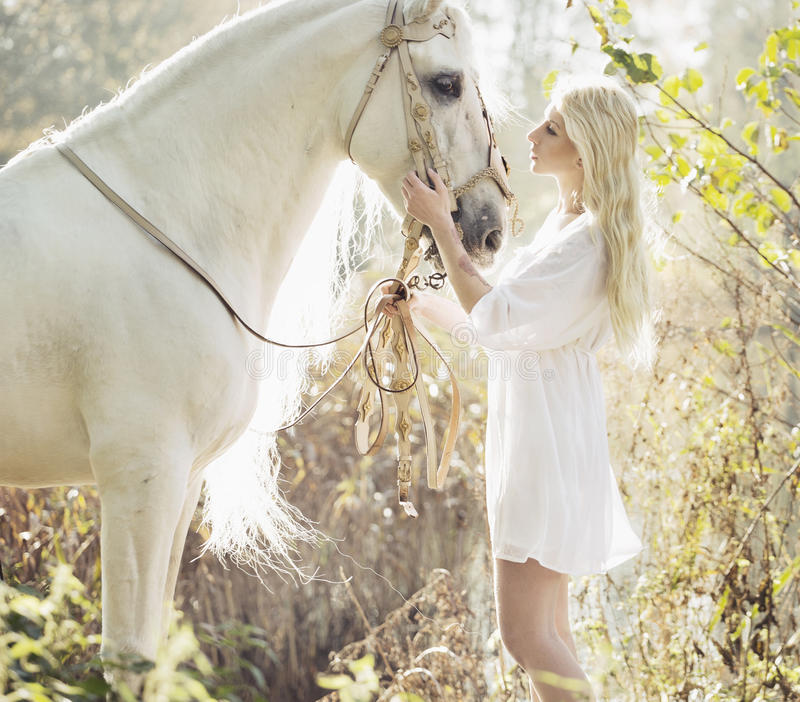 Blonde beautiful woman touching mejestic horse royalty free stock photography