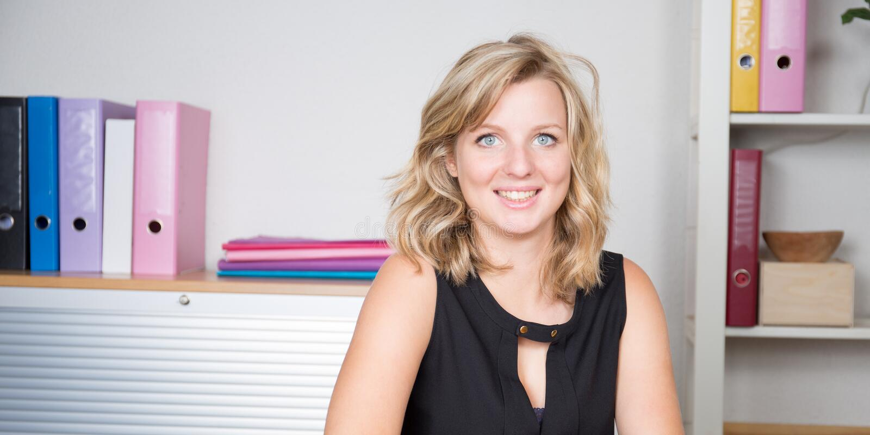 blonde bedrijfsvrouwenzitting door de lijst die camera in bureau bekijken royalty-vrije stock foto