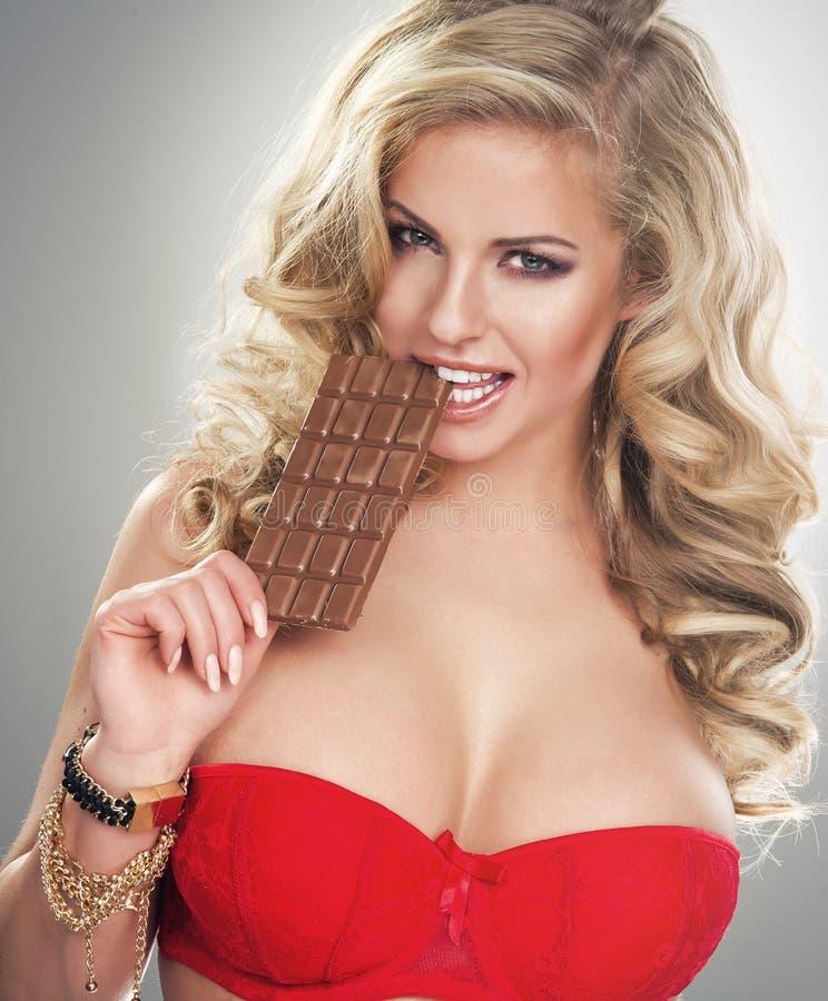blonde beißende Schokolade der jungen Frau lizenzfreies stockbild