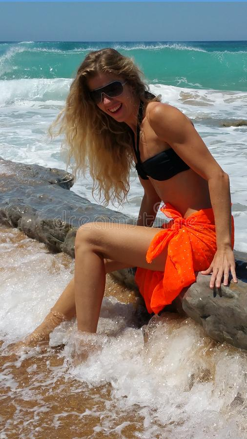 Blonde in a black bikini and sunglasses and orange pareo royalty free stock photo