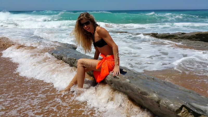 Blonde in a black bikini and sunglasses and orange pareo on the beach royalty free stock photo