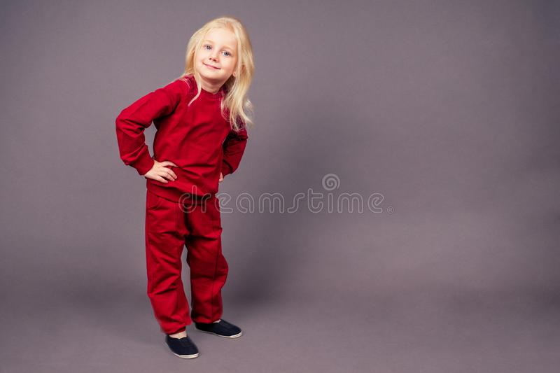 Blonde blue-eyed little model girl in a red sports suit posing in the studio on a black background.active childhood full. Length portrait sporty costume royalty free stock image