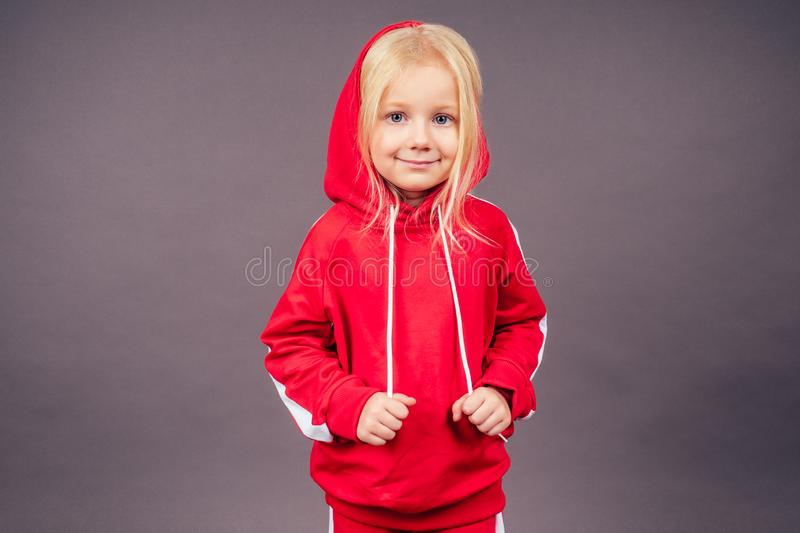 Blonde blue-eyed little model girl in a red sports suit posing in the studio on a black background.active childhood full. Length portrait put on hood on head royalty free stock images