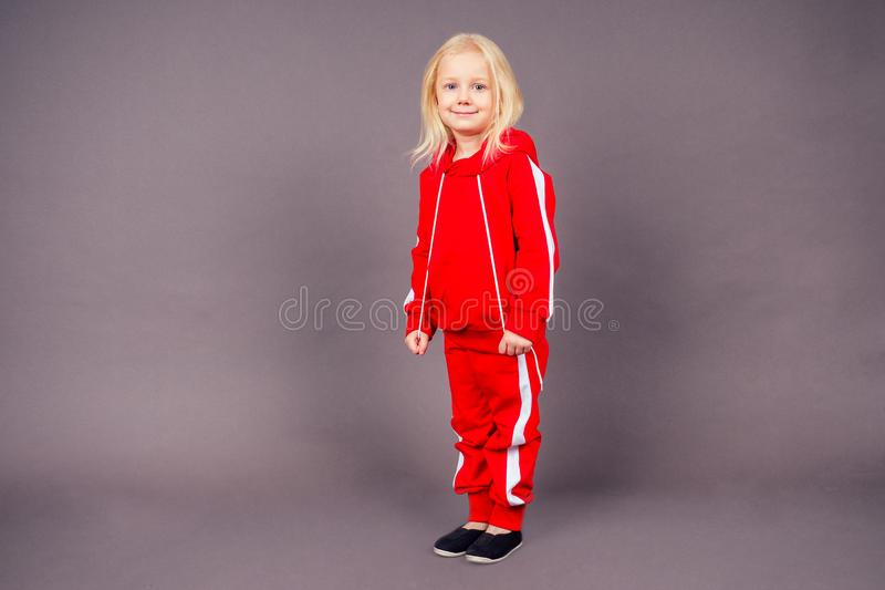 Blonde blue-eyed little model girl in a red sports suit posing in the studio on a black background.active childhood full. Length portrait sporty costume hip-hop stock photography