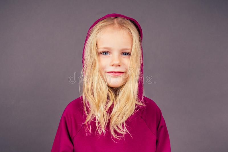 Blonde blue-eyed little model girl in a violet sports suit posing in the studio on a black background.active childhood. Full length portrait put on hood on head royalty free stock image