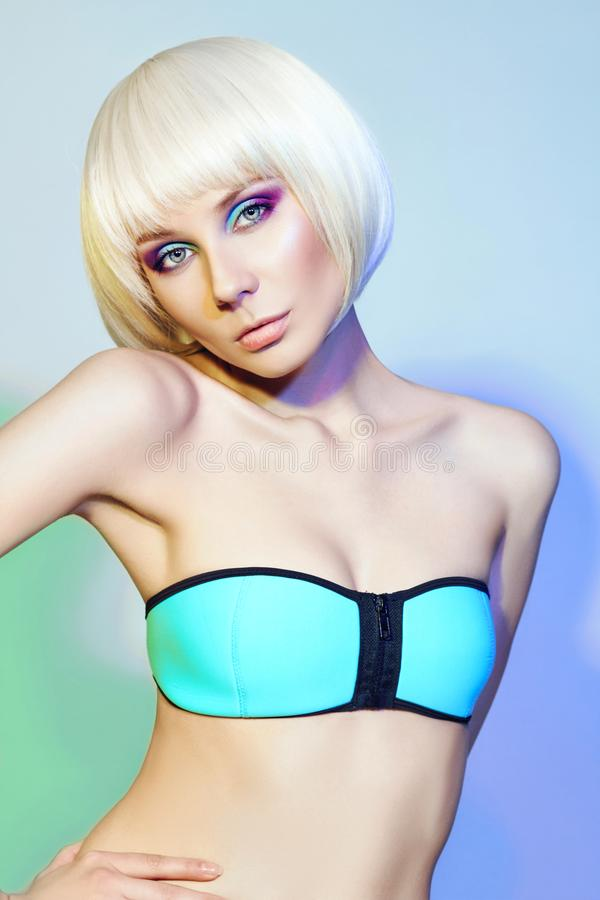 Blonde in the blue swimsuit with bright contrasting make-up on w. Hite background with contrast coloured spots. Fashion makeup beauty and skin care. Daring and royalty free stock photos