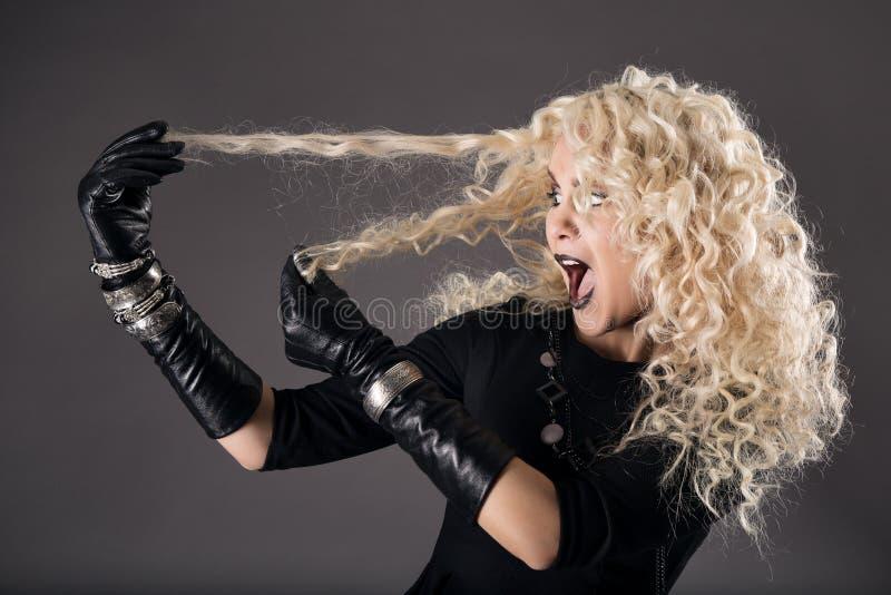 Blonde bouclée de coiffure dans le noir, perte de poils de femme, prob de coloration photos libres de droits