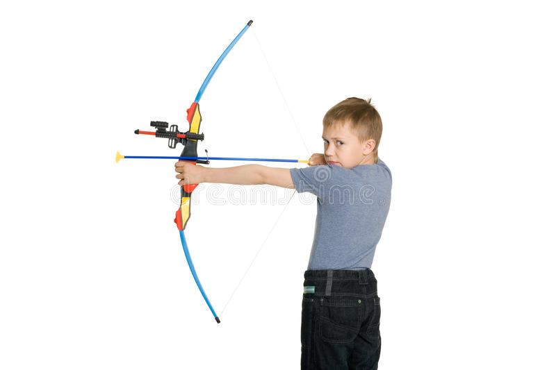 Blonde boy shoot from the crossbow stock image