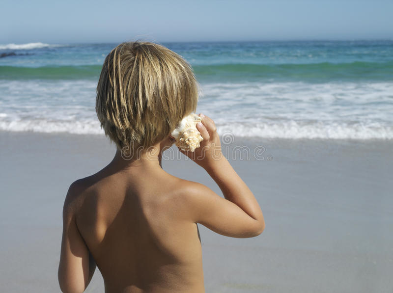 Blonde boy (5-7) standing on beach, listening to sea shell, looking at horizon over sea, rear view royalty free stock photo