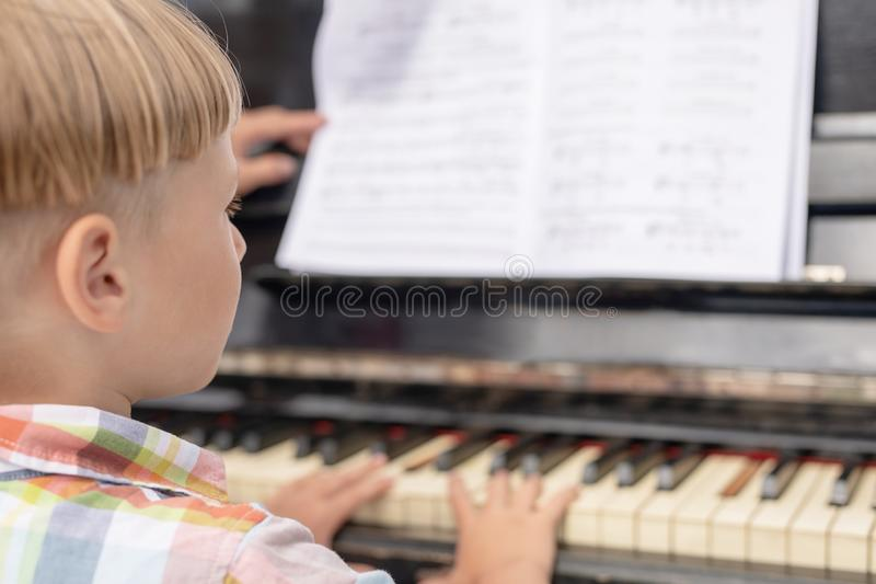 Blonde boy 5 years old, preschooler playing the piano, view from the back royalty free stock photo