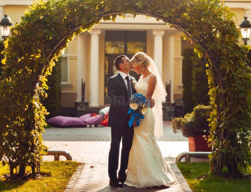 blonde Braut mit einem Blumenstrauß von Blumen in ihren Händen und ihr Verlobtes stehen nahe einem natürlichen Bogen stockfoto