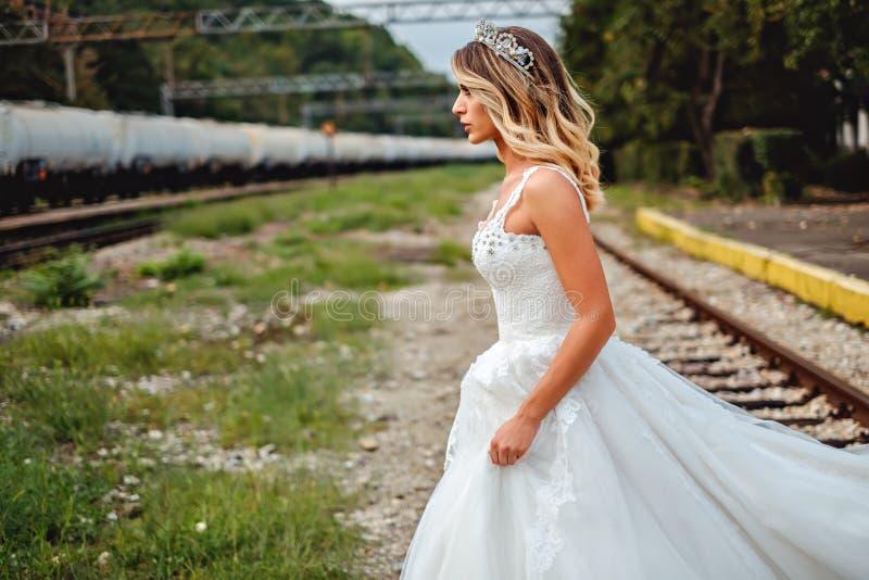 Blonde Braut, welche die Schiene kreuzt stockfoto