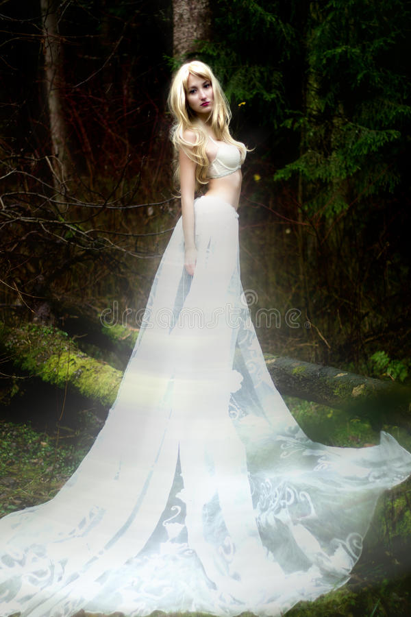Free Blonde Bride Angel In Long White Skirt Standing In Dark Forest Stock Photo - 36040060