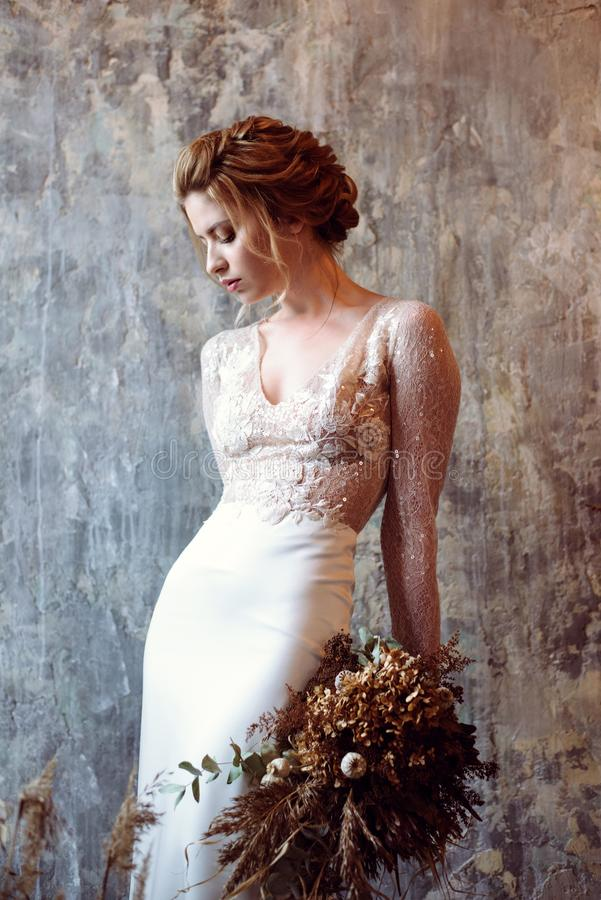 Blonde bride in fashion white wedding dress with makeup. Wedding day of bride in bridal gown. Beauty woman and bouquet. Fashion blonde model indoors. Beauty royalty free stock image
