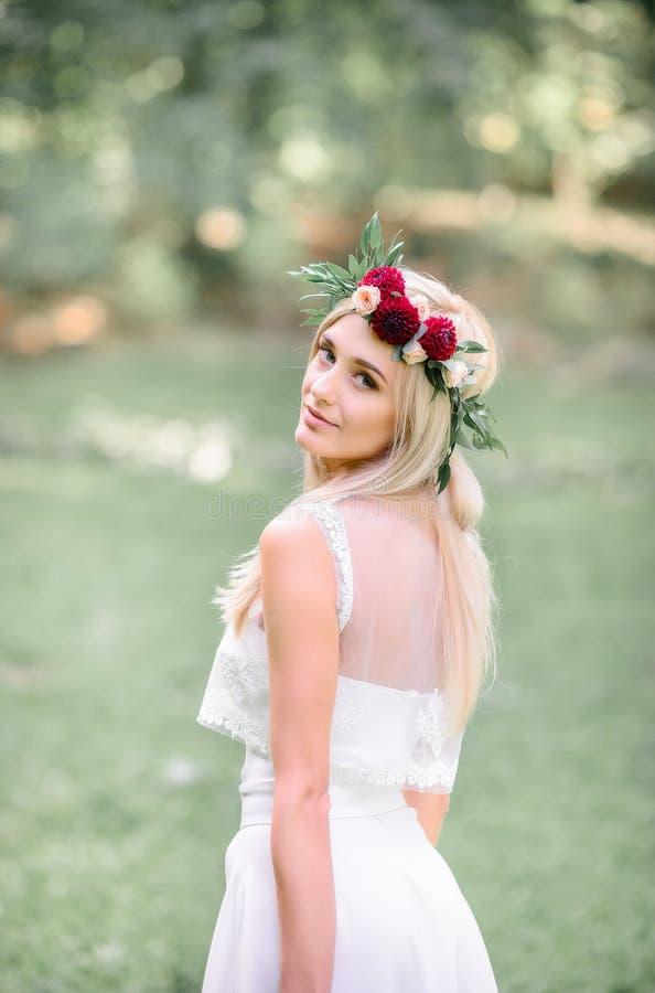 Blonde bride looks over her tender shoulder while posing royalty free stock image