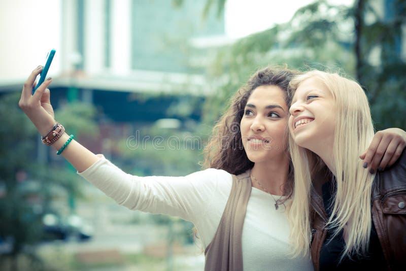 Blonde and brunette beautiful stylish young women stock image