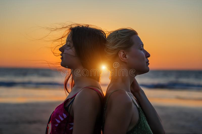 Blonde and brunette girlfriends are clinging back to each other against sunset over the sea. Happy lesbian european couple is stock photo