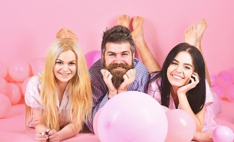 Blonde and brunette on smiling faces have fun with bearded macho. Best friends, lovers near balloons, pink background stock image