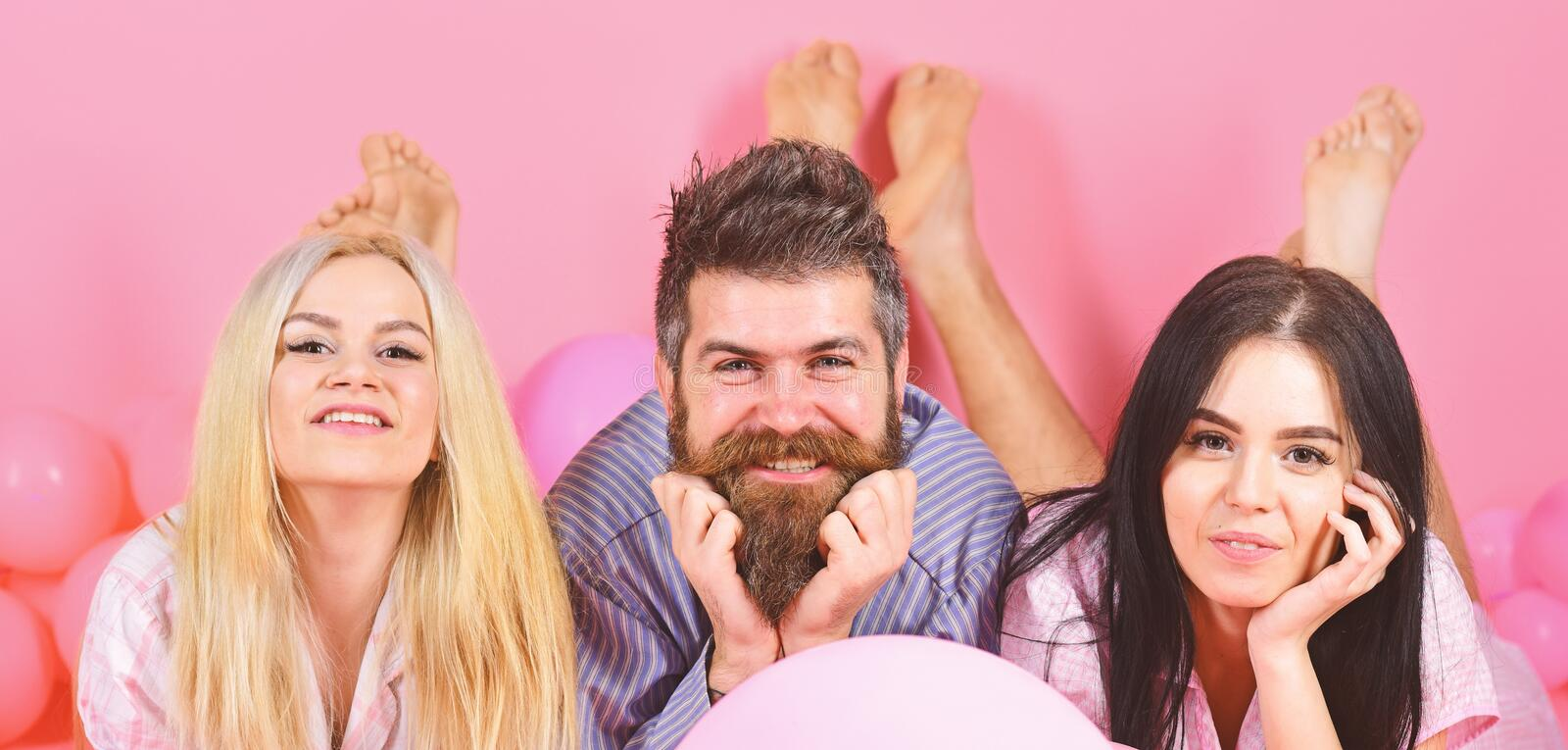 Blonde and brunette on smiling faces have fun with bearded macho. Gossip concept. Best friends, lovers near balloons royalty free stock images