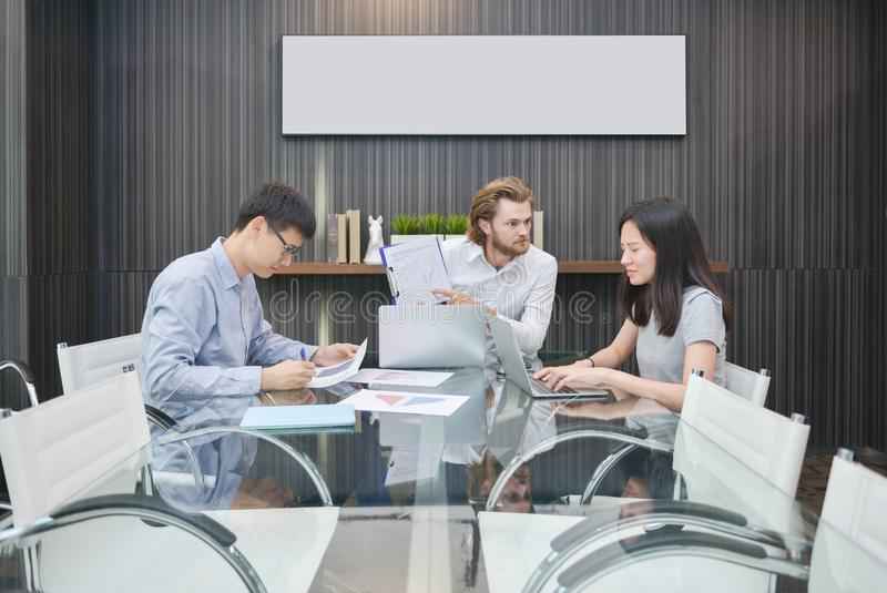 Blonde business man blaming Asian employee in meeting room stock photos