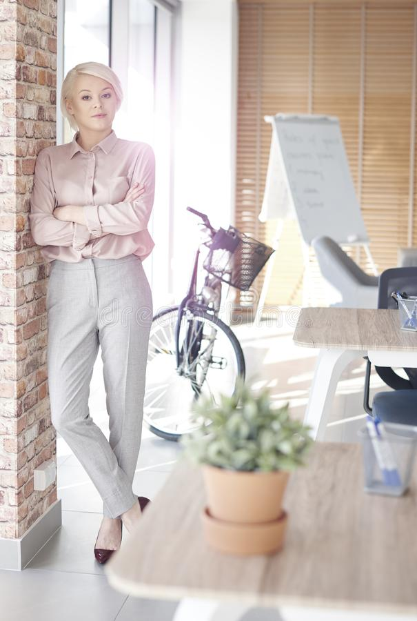 Blonde business woman in the office stock images