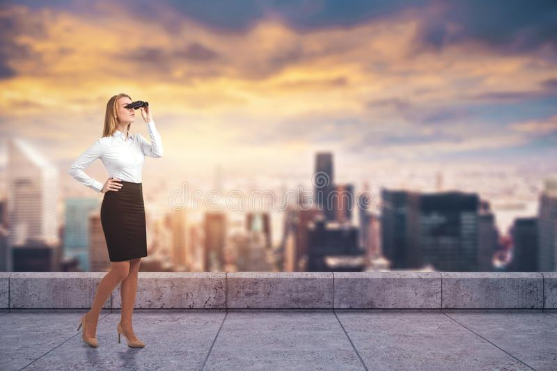 Businesswoman with binoculars on city roof royalty free stock photo