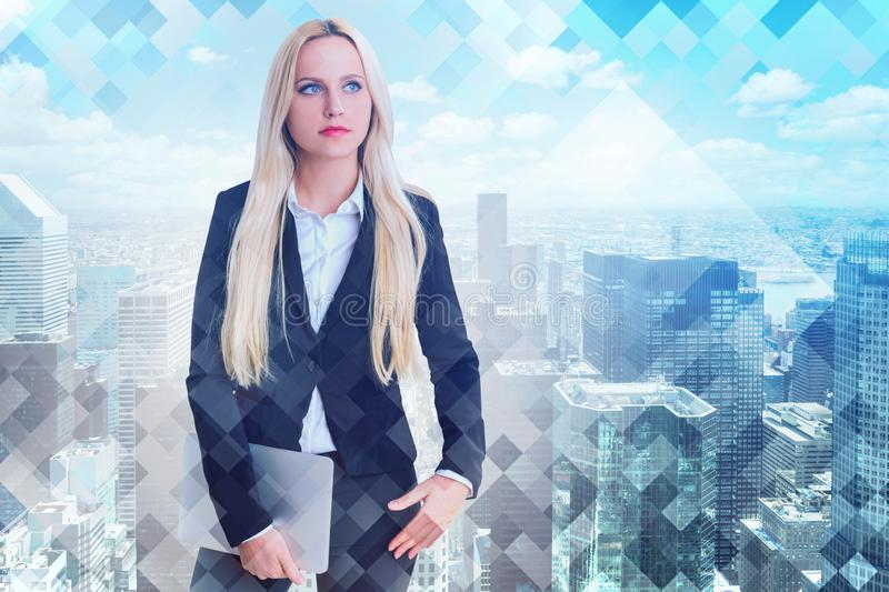 Blonde businesswoman with laptop in city royalty free stock photography