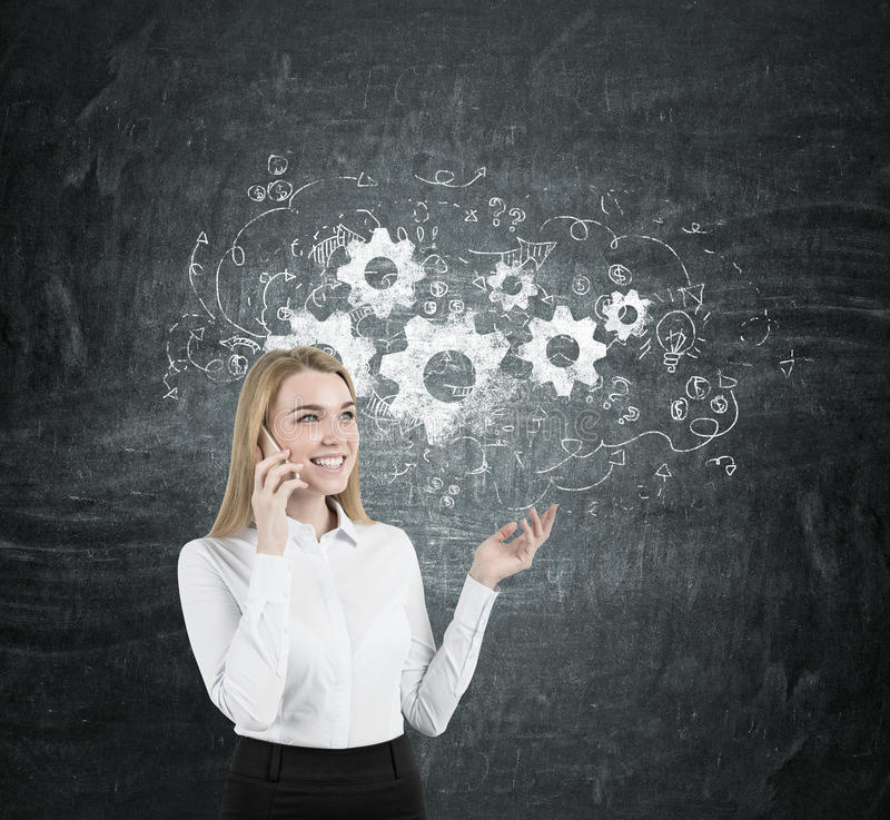 Blonde businesswoman on a phone, gears. Portrait of a young blonde businesswoman wearing a white shirt and talking on a cell phone and gesticulating. Blackboard stock photography