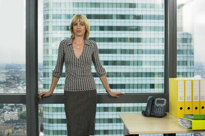 Blonde businesswoman standing beside office window, smiling, front view, portrait stock photo