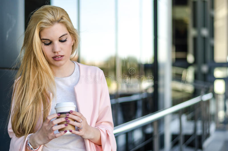 blonde businesswoman or student with coffee isolated smiling portrait close up street. stock photos