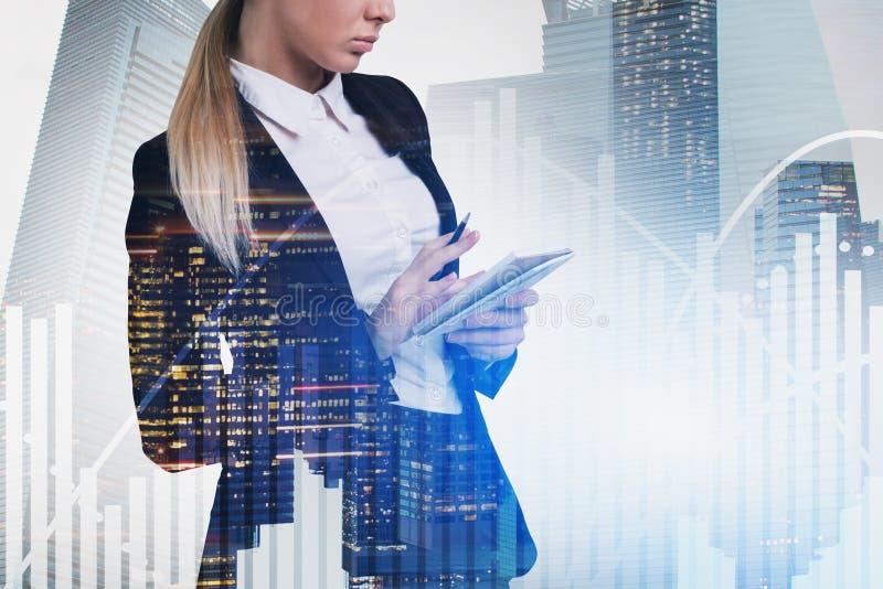 Blonde businesswoman writing report, graphs stock photos