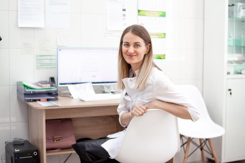 Blonde caucasian woman doctor in white uniform in clinic hospital works on computer and smiles at camera. Cabinet and stock images