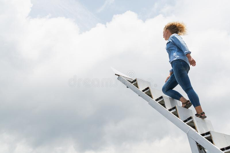 Blonde Caucasian woman walking up the stairs to the sky with clouds on background royalty free stock image
