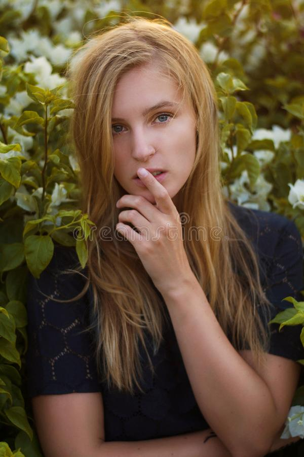 Close up of blonde caucasian woman wearing dark blue lace top. Posing between white flowers in Egypt. royalty free stock photography