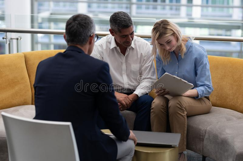 Blonde Caucasians businesswoman signing documents while sitting on the sofa. Front view of young blonde Caucasians businesswoman signing documents while sitting stock image