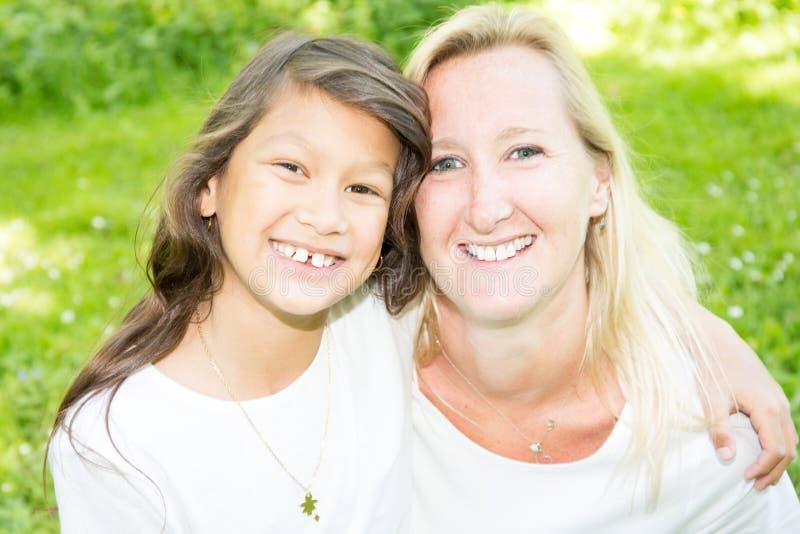 Blonde caucasienne de jeune mère mélangée heureuse de famille avec la fille sud-américaine indienne image stock
