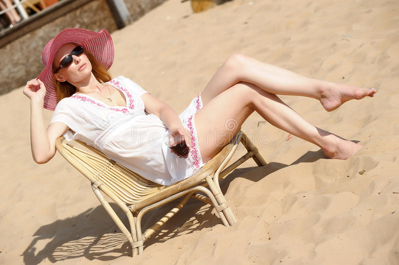 Blonde in a chaise longue on the beach. Wearing a hat with a glass of wine stock photo